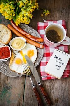 Desayuno con salchichas, huevos y taza de té.