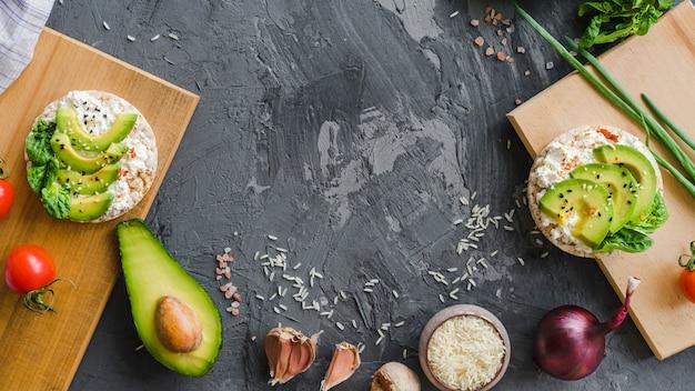 Desayuno saludable con aguacate; ajo; arroz; tomate cherry y cebolla en textura de cemento
