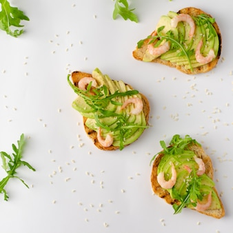 Desayuno saludable con aguacate en rodajas, shrimas y rúcula en pan tostado sobre fondo blanco. endecha plana,.
