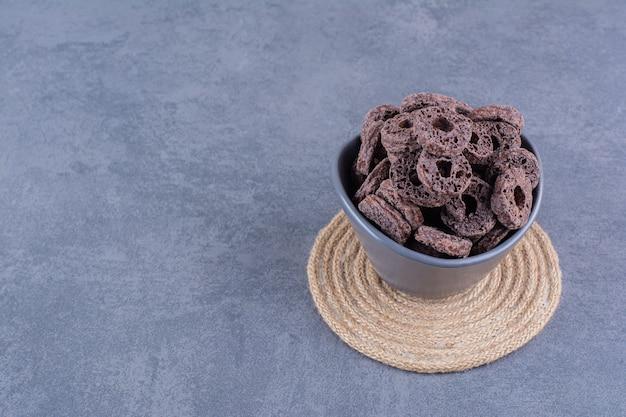 Desayuno saludable con anillos de maíz de chocolate en un cuenco negro sobre piedra.