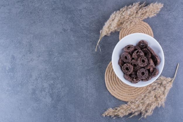 Desayuno saludable con anillos de maíz de chocolate en un plato sobre una superficie de piedra
