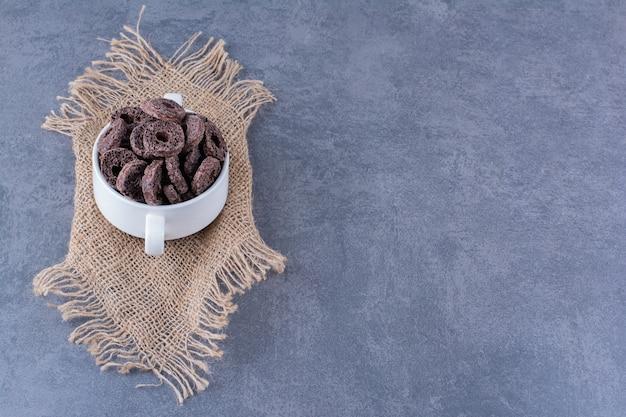 Desayuno saludable con anillos de maíz de chocolate en un recipiente blanco sobre piedra.