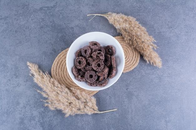 Desayuno saludable con aros de maíz chocolate en un plato sobre piedra.