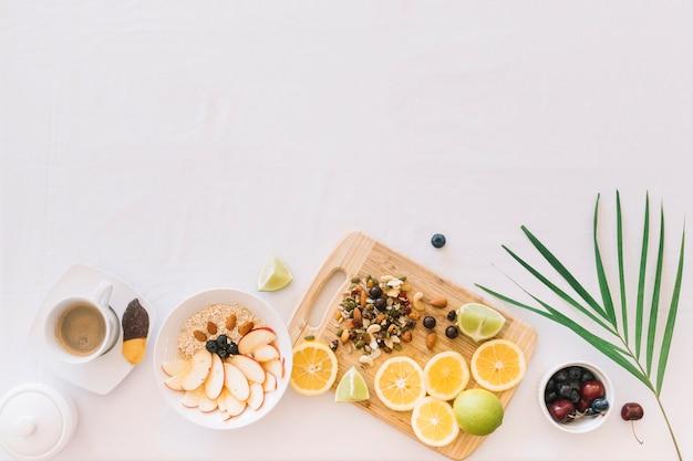 Desayuno saludable con avena; frutas y frutos secos sobre fondo blanco