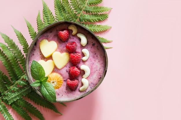 Desayuno saludable batido de plátano y arándano decorado con frutas en un tazón de coco en rosa.