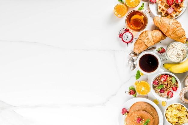Desayuno saludable concepto de comer varios alimentos de la mañana - panqueques waffles croissant sándwich de avena y granola con yogur fruta bayas café té jugo de naranja fondo blanco