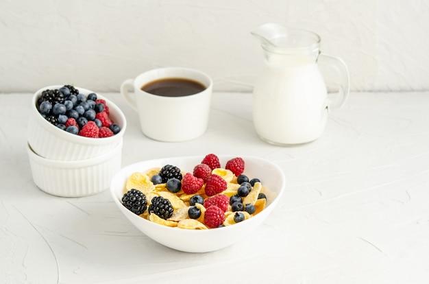 Desayuno saludable con copos de maíz, frambuesas, moras, arándanos, leche y café sobre una superficie blanca.