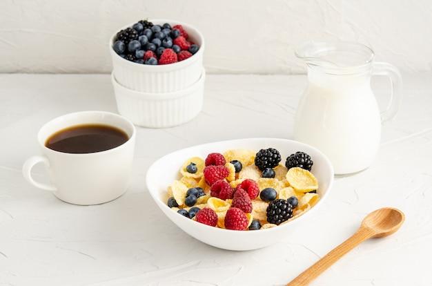 Desayuno saludable con copos de maíz en un plato blanco, bayas, leche y café.