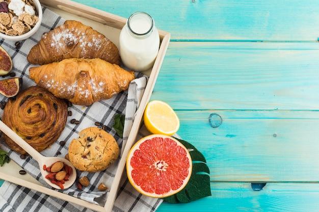 Desayuno saludable con croissant; cookies respaldadas leche; muesli; y cítricos en bandeja de madera.