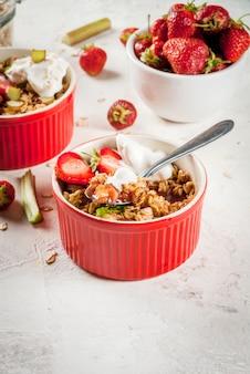 Desayuno saludable. crumble de avena y granola con ruibarbo, fresas y moras frescas, semillas y helado en cuencos horneados, decorados con menta, en una mesa de hormigón de piedra blanca, espacio de copia