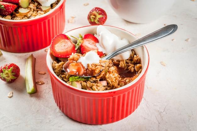Desayuno saludable. crumble de avena y granola con ruibarbo, fresas y moras frescas, semillas y helado en tazones horneados, decorados con menta, sobre mesa de piedra blanca de hormigón, copyspace