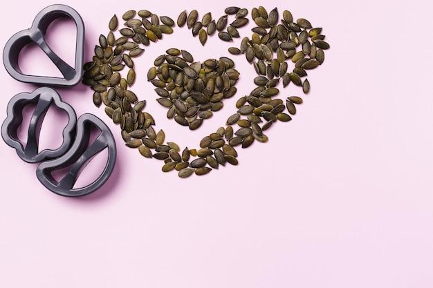 Desayuno saludable. forma para galletas y un corazón de semillas de calabaza sobre fondo rosa.