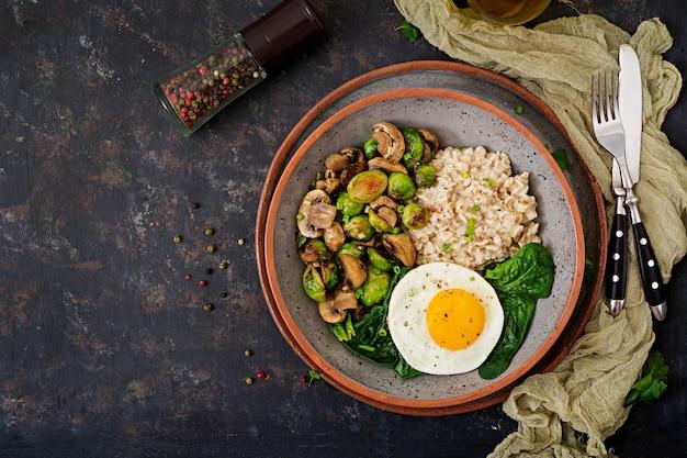 Desayuno saludable. gachas de avena, huevo y ensalada de verduras al horno: champiñones y coles de bruselas. vista superior