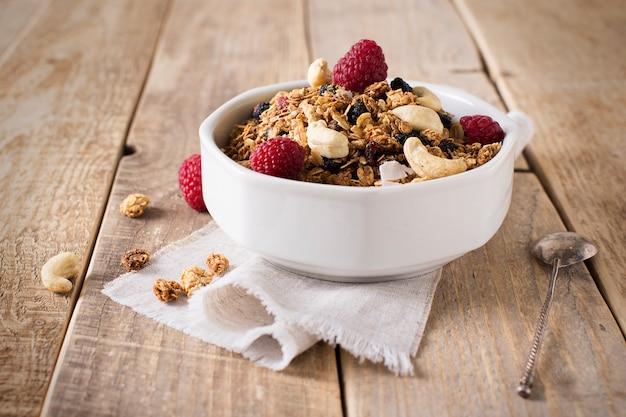 Desayuno saludable con granola de avena, frambuesa y nueces sobre una mesa de madera