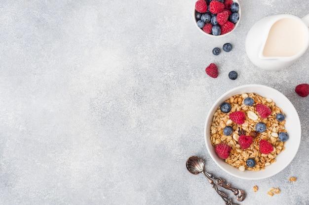 Desayuno saludable. granola fresca, muesli con yogur y bayas sobre fondo gris.