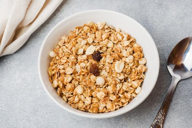 Desayuno saludable. granola fresca, muesli con yogur sobre fondo gris.