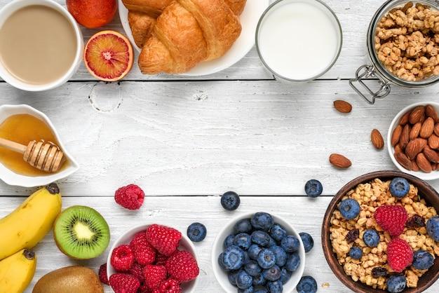 Desayuno saludable con granola muesli, frutas, bayas, nueces, croissant y una taza de café.