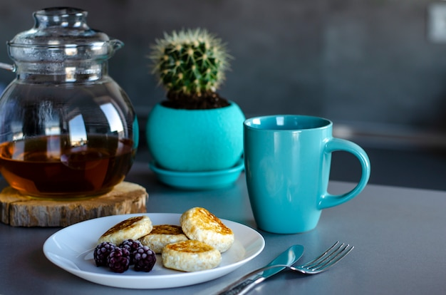 Desayuno saludable hecho de panqueques de requesón con bayas y té verde en una tetera de vidrio.