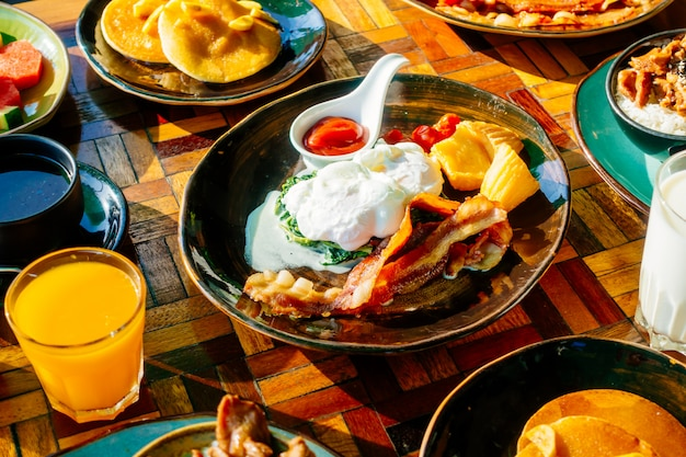 Desayuno saludable con huevo, panceta, pancakes, jugo de naranja, leche, pan y café
