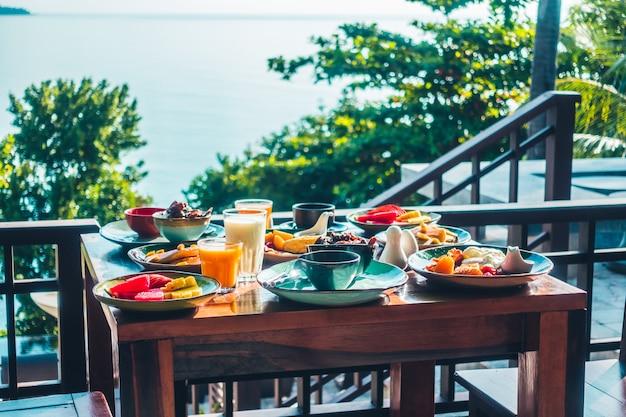 Desayuno saludable con huevo, panceta, panqueques, jugo de naranja, leche, pan y café