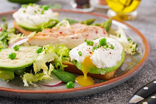 Desayuno saludable. huevos escalfados sobre tostadas con aguacate, espárragos y filete de pollo a la parrilla.