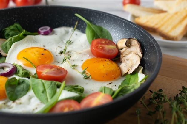 Desayuno saludable con huevos fritos, tomates, champiñones y hojas de espinaca.