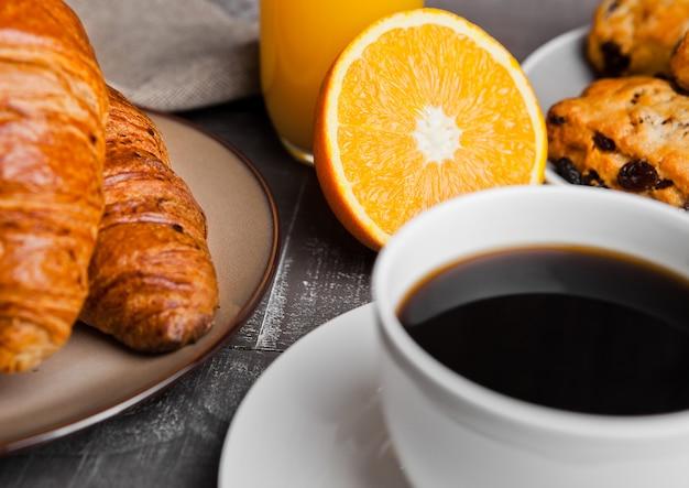 Desayuno saludable con jugo de café frutas pastelería en mesa de madera