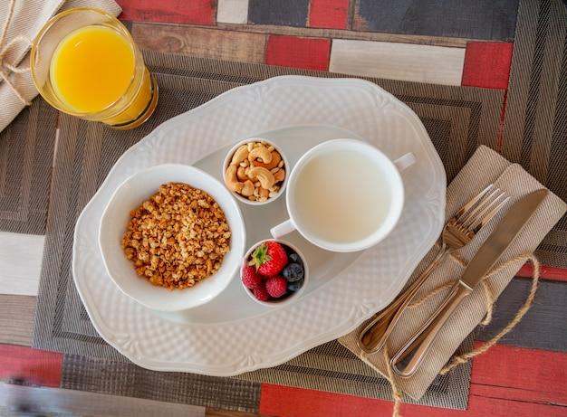 Desayuno saludable con jugo fresco y muesli con leche y bayas.