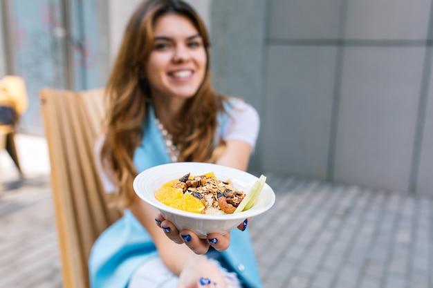 Desayuno saludable en manos de una mujer joven sentada en una silla
