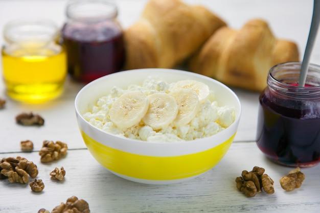 Desayuno saludable: migajas, requesón con plátano, nueces, croissants, miel y mermelada de arándanos rojos en un recipiente sobre una mesa de madera