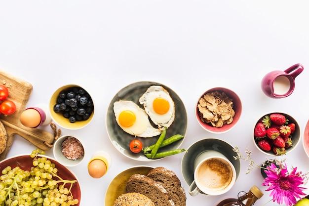 Desayuno saludable con muesli, frutas, nueces sobre fondo blanco