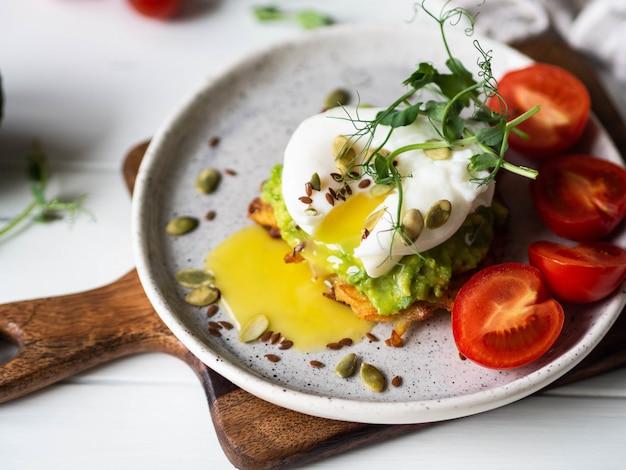 Desayuno saludable y nutritivo de panqueques de papa, puré de aguacate, huevo escalfado, brotes de guisantes y varias semillas en un plato de cerámica