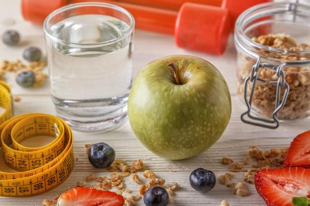 Desayuno saludable, pesas y cinta métrica sobre superficie de madera
