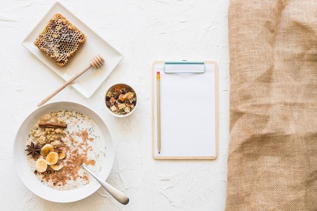 Desayuno saludable con portapapeles y lápiz sobre fondo blanco