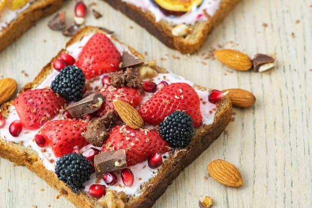 Desayuno saludable. rebanada de tostada integral con queso crema, fresas, nueces y mora. vista superior