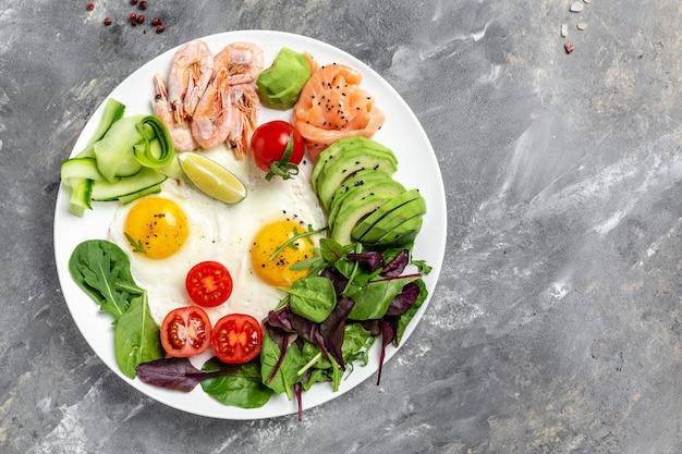 Desayuno saludable con salmón, camarones cocidos, gambas, huevos fritos, ensalada fresca, tomates, pepinos y aguacate. dieta cetogénica. lugar de la receta del menú para el texto, vista superior.