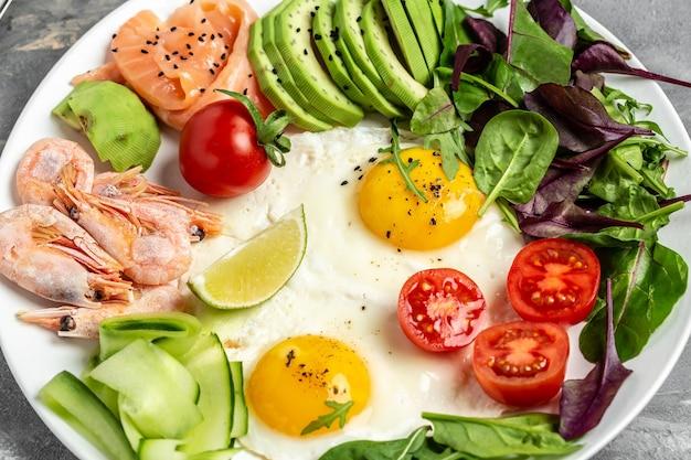 Desayuno saludable con salmón, camarones cocidos, gambas, huevos fritos, ensalada fresca, tomates, pepinos y aguacate. dieta cetogénica. vista superior.