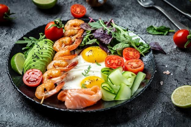 Desayuno saludable con salmón, camarones a la plancha, gambas, huevos fritos, ensalada fresca, tomates, pepinos y aguacate. dieta cetogénica. vista superior.