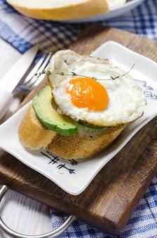 Desayuno saludable. sandwich con pan de centeno, aguacate y huevos fritos.