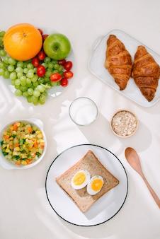 Desayuno saludable servido con leche, croissants, huevo, cereales, avena y frutas.