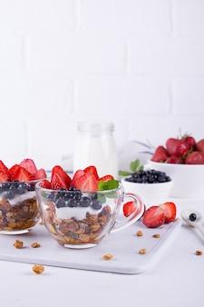 Desayuno saludable en una taza con granola horneada casera, bayas frescas y yogur sobre un fondo blanco de mesa