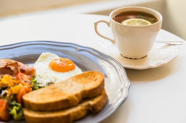Desayuno saludable y taza de té en mesa blanca