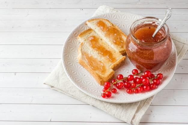 Desayuno saludable con tostadas, mermelada y grosellas rojas