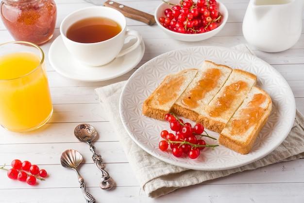 Desayuno saludable con tostadas, mermelada, jugo de naranja fresco y grosellas rojas