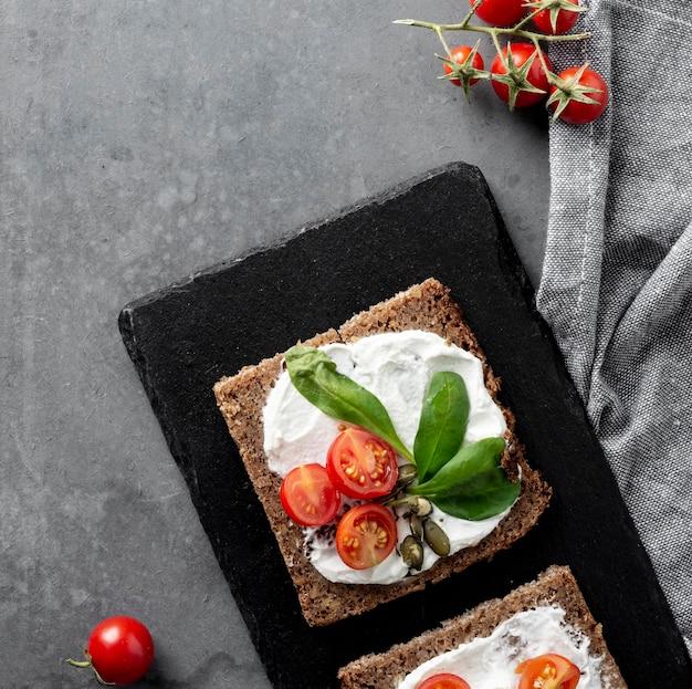 Desayuno saludable con tostadas y tomates en tabla de cortar