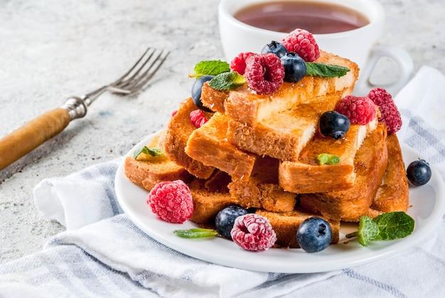 Desayuno saludable de verano, palitos de pan tostado francés con bayas frescas y miel, superficie de piedra gris claro de la mañana