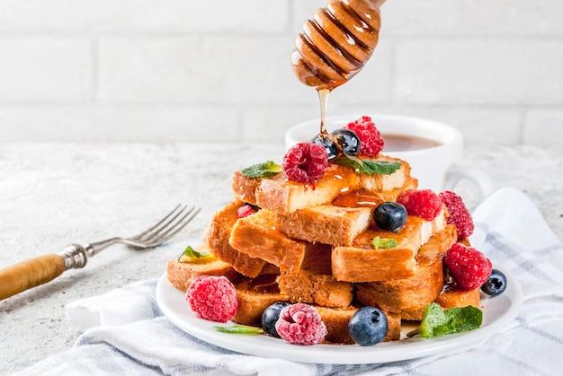 Desayuno saludable de verano, palitos de pan tostado francés con bayas frescas y miel,