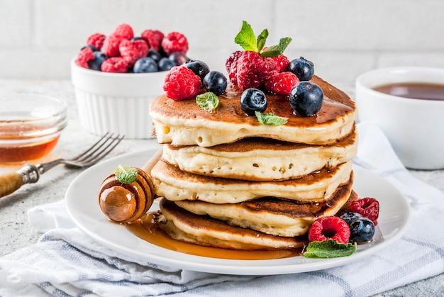 Desayuno saludable de verano, panqueques americanos clásicos caseros con bayas frescas y miel, superficie de piedra gris claro de la mañana