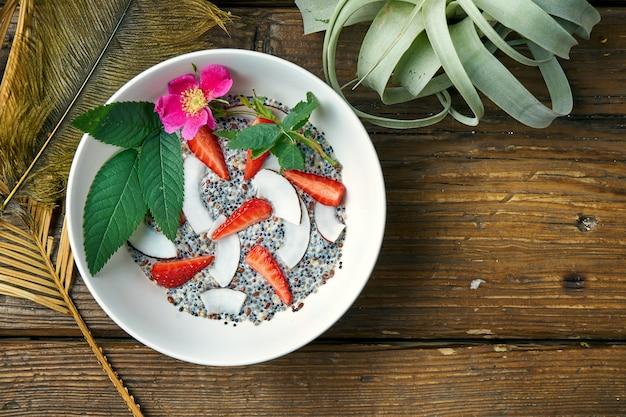 Desayuno saludable: yogurt con una mezcla de cereales, semillas de chia, fresas con leche de coco en un tazón sobre una madera