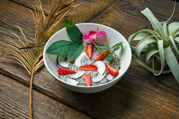 Desayuno saludable: yogurt con una mezcla de cereales, semillas de chia, fresas con leche de coco en un tazón sobre una mesa de madera